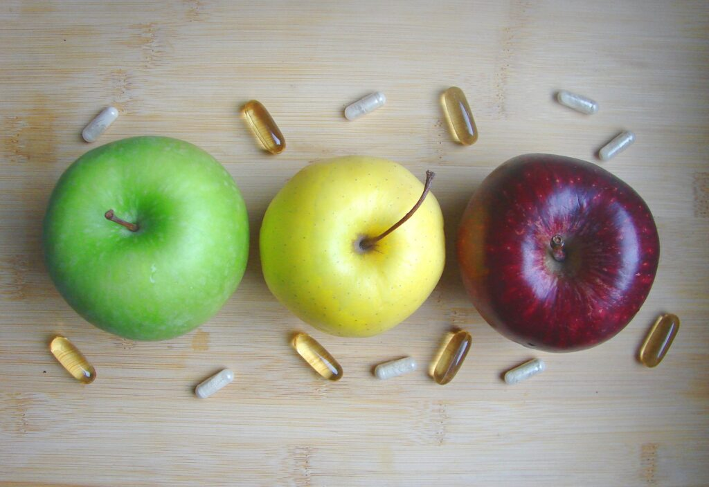 Three apples, green, yellow and red. Pills are aroung them