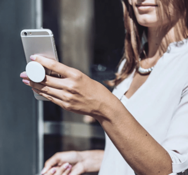 Woman is holding a cell phone, with a hand holder